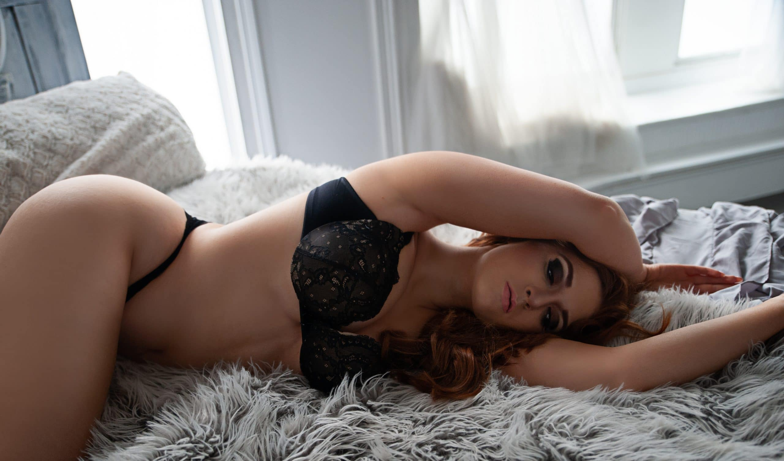 Woman posing for boudoir photoshoot on bed